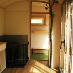 Innenraum mit Holzofen und Durchgang zur Garderobe